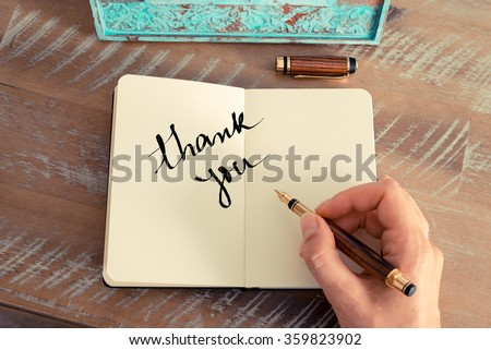 Retro effect and toned image of a woman hand writing a note with a fountain pen on a notebook. Motivational concept with handwritten text THANK YOU - stock photo