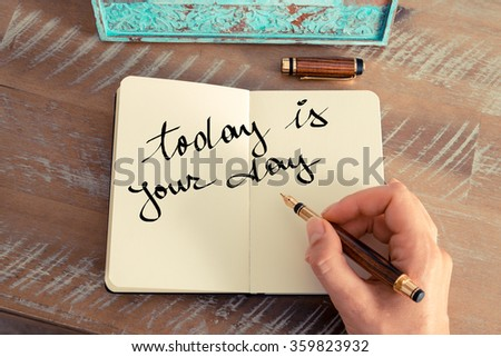 Retro effect and toned image of a woman hand writing a note with a fountain pen on a notebook. Motivational concept with handwritten text TODAY IS YOUR DAY - stock photo