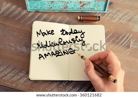 Retro effect and toned image of a woman hand writing a note with a fountain pen on a notebook. Motivational concept with handwritten text MAKE TODAY RIDICULOUSLY AMAZING - stock photo