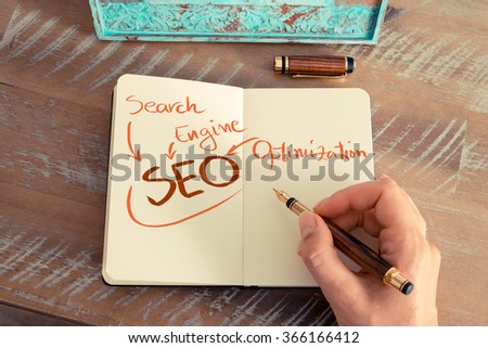 Retro effect and toned image of a woman hand writing a note with a fountain pen on a notebook. Handwritten text SEO as SEARCH ENGINE OPTIMIZATION, business success concept - stock photo
