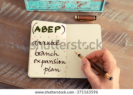 Retro effect and toned image of a woman hand writing a note with a fountain pen on a notebook. Business acronym ABEP Annual Branch Expansion Plan with handwritten text - stock photo
