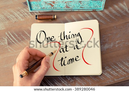 Retro effect and toned image of a woman hand writing a note with a fountain pen on a notebook. Handwritten text One Thing At A Time as business concept image - stock photo