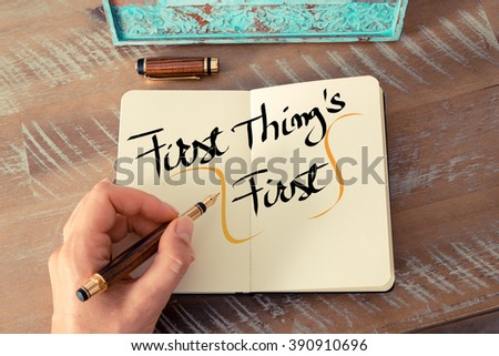 Retro effect and toned image of a woman hand writing a note with a fountain pen on a notebook. Handwritten text First Thing's First as business concept image - stock photo