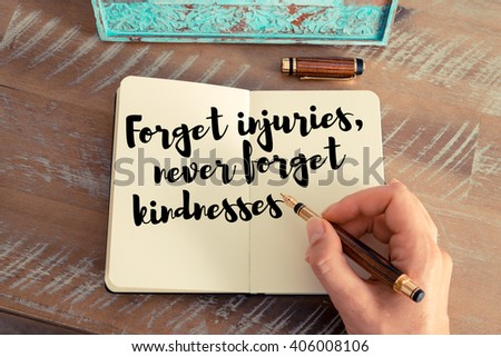 Retro effect and toned image of a woman hand writing on a notebook. Handwritten quote Forget injuries, never forget kindnesses as inspirational concept image - stock photo