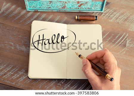 "Retro effect and toned image of woman hand writing a note on a notebook. Handwritten text in German ""Hallo""  - translation : Hello as business concept image"