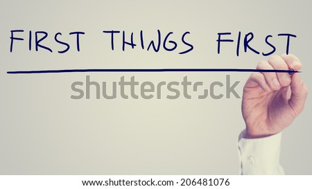 Retro effect concept - First Things First - with a man writing the words on a virtual interface with a marker pen over white with copyspace conceptual of prioritizing tasks. - stock photo