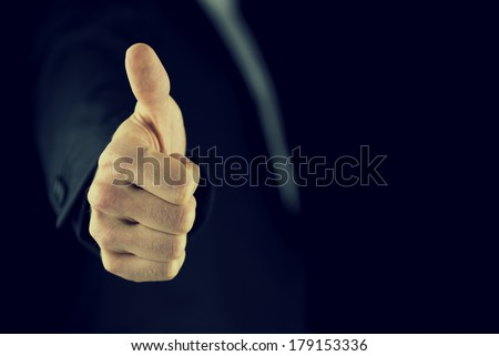 Retro effect faded and toned image of a businessman giving a thumbs up gesture of approval and success, with copyspace. - stock photo