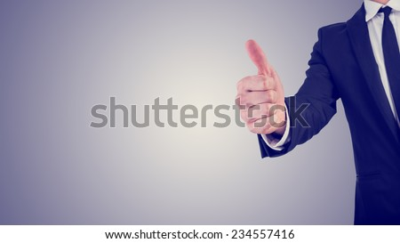 Retro effect faded and toned image of a businessman giving a thumbs up gesture of approval and success,  with plenty of copyspace in a business motivation concept. - stock photo