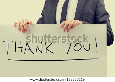 Retro effect faded and toned image of a businessman holding a billboard with Thank you! sign on it. - stock photo