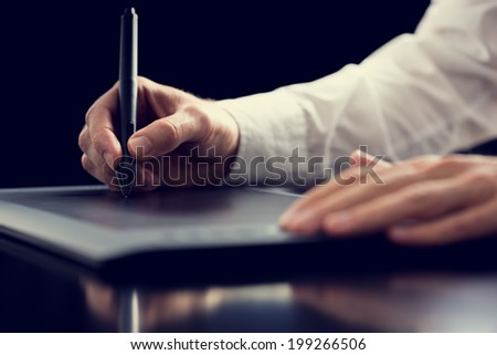 Retro effect faded and toned image of a graphic designer working with digital tablet pen, over black background. - stock photo