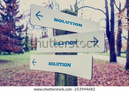 Retro effect faded and toned image of a rural signboard with the word Solution with arrows pointing in three directions. - stock photo