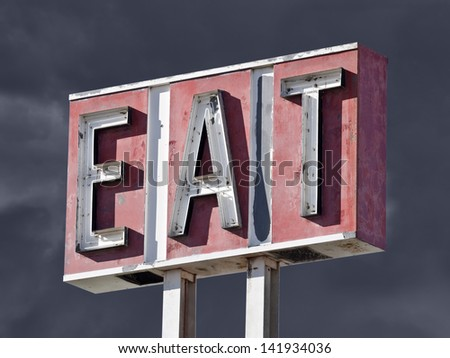 Retro faded eat sign with thunderstorm sky. - stock photo