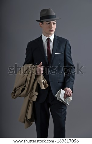 Retro fashion fifties young man with hat wearing dark suit and tie. Holding a raincoat and newspaper. Studio shot against grey. - stock photo
