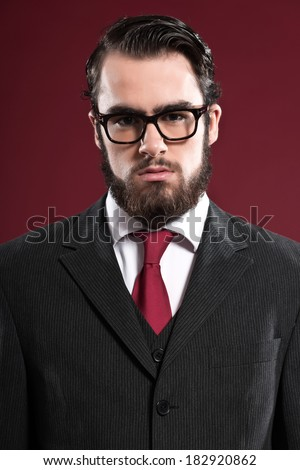 Retro 1900 fashion man with beard wearing grey suit red tie and glasses. Studio shot.