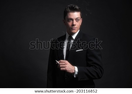 Retro fifties fashion man smoking a cigarette. Wearing black suit and tie. Studio shot.