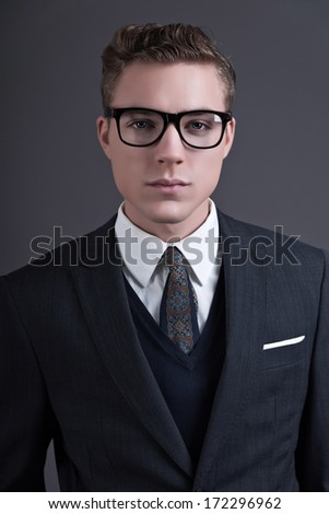 Retro fifties fashion young businessman with black glasses wearing dark suit and tie. Studio shot against grey.
