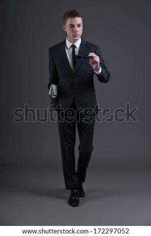 Retro fifties fashion young businessman with newspaper holding black sunglasses wearing dark suit and tie. Studio shot against grey.