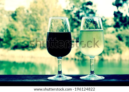 Retro filter style two glasses of wine, white and red, on wooden rail with country rural scene in background. - stock photo