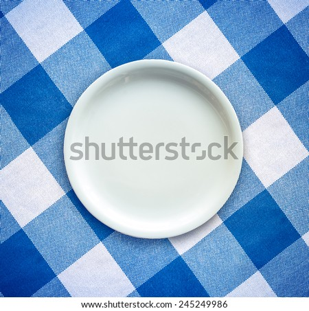Retro Filtered Empty White Plate On A Checked Table Cloth - stock photo