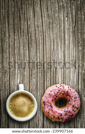Retro Filtered Image Of A Pink Donut And A Cup Of Coffee On A Rustic Wooden Table With Copy Space - stock photo