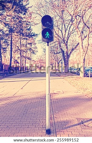 Retro filtered photo of traffic lights, green color. - stock photo