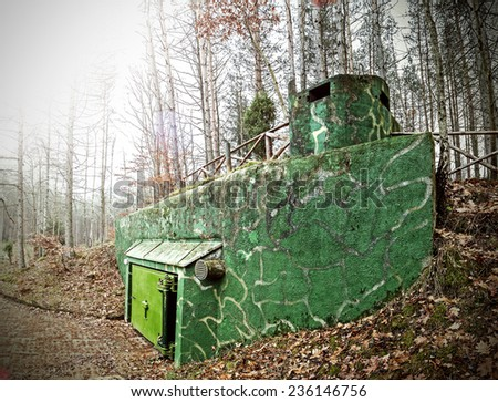 Retro filtered picture of a bunker hidden in forest. - stock photo