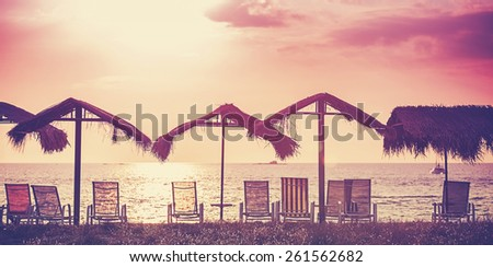 Retro filtered picture of beach chairs and umbrellas at sunset. Concept for rest, relaxation, holidays.  - stock photo
