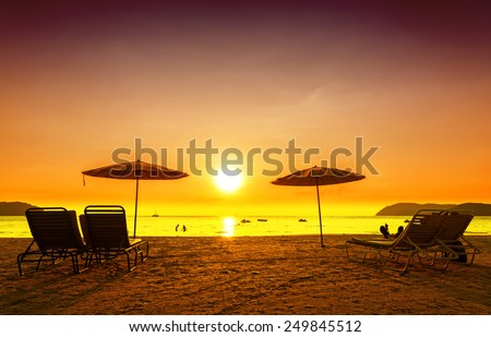 Retro filtered picture of beach chairs and umbrellas on sand at sunset. Concept for rest, relaxation, holidays.  - stock photo
