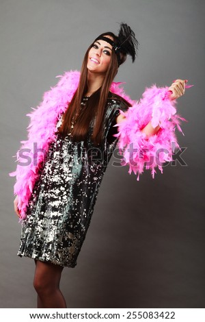 Retro flapper woman on carnival time. Young female pink plume black feather on head and sequin glossy evening dress - stock photo