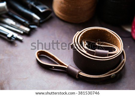 Retro genuine leather camera strap on leather texture background