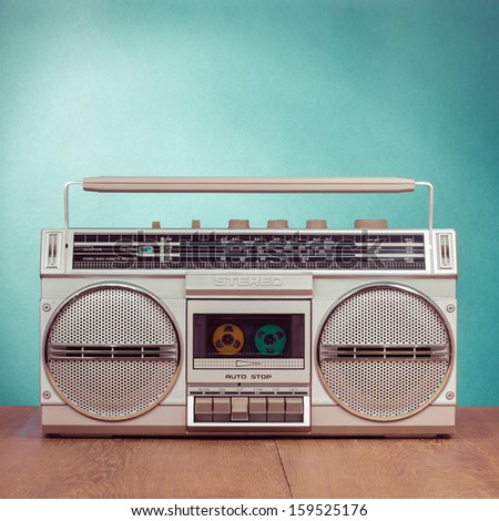 Retro ghetto blaster cassette tape recorder on table in front mint green background - stock photo
