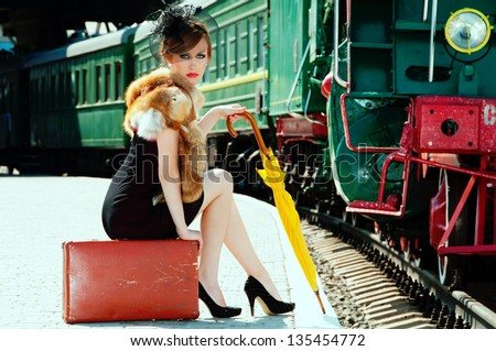 Retro girl sitting on suitcase at the train station - stock photo