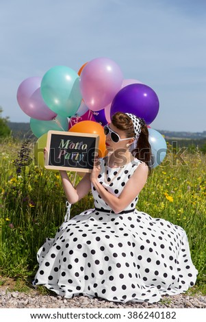 Retro Girl with a petticoat dress and sunglasses holding a board with text Motto Party, concept invitation and theme party - stock photo