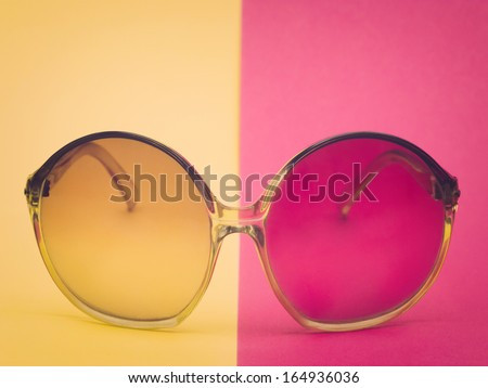 Retro glasses on yellow and pink surface - stock photo
