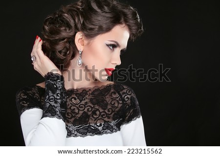 Retro hairstyle. Beautiful Brunette Woman. Fashion portrait with red lips and manicured nails. Isolated on black background. - stock photo