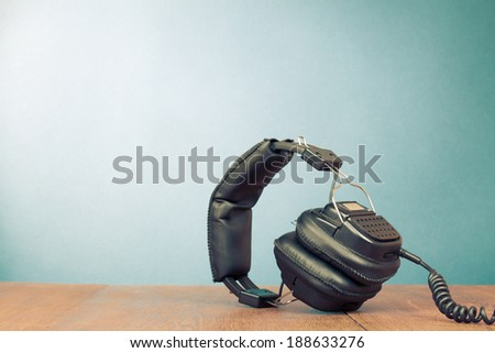 Retro headphones on table front mint green wall background - stock photo