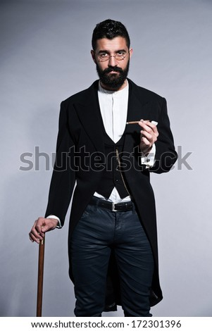 Retro hipster 1900 fashion man with black hair and beard. Standing with walking cane. Smoking cigar. Wearing vintage glasses. Studio shot against grey.
