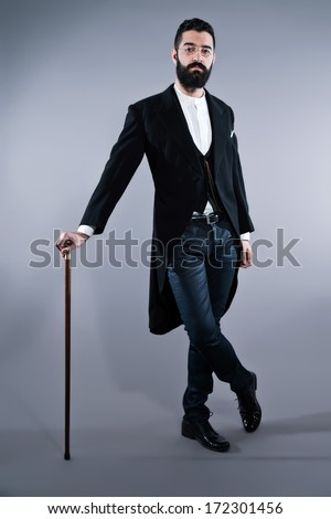 Retro hipster 1900 fashion man with black hair and beard. Standing with walking cane. Wearing vintage glasses. Studio shot against grey.