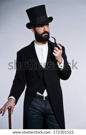 Retro hipster 1900 fashion man with black hair and beard. Wearing black hat. Standing with cane. Smoking pipe. Studio shot against grey.