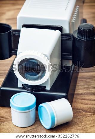 Retro home cine-projector. Vintage still life. Closeup photo. Entertainment theme. - stock photo