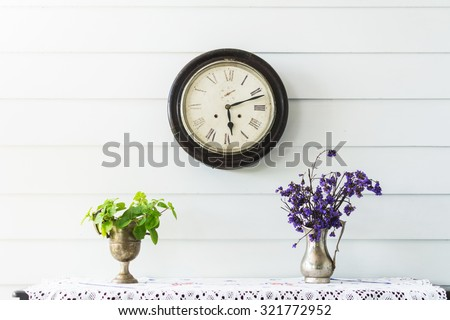 Retro home decor. Flowers and a vintage clock on a white wall shelf. - stock photo