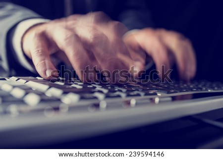 Retro image of a businessman typing on a computer keyboard inputting data with motion blur. - stock photo
