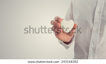 Retro image of a man holding a white heart. Concept of Valentines, love or romance, with copyspace to the left. - stock photo