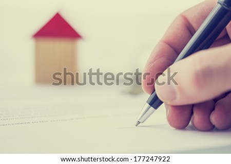 Retro image of a man signing a deed of sale, mortgage document or insurance contract on a house with a closeup view of his hand with a small wooden model of a house. - stock photo