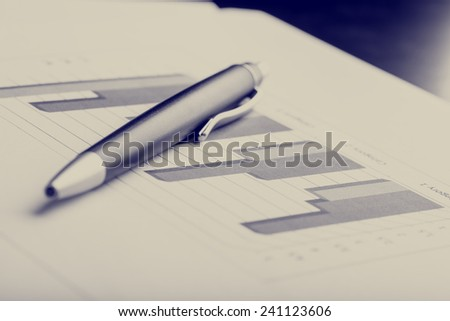 Retro image of ballpoint pen next to a printed 3d column chart, used to present data and trends in statistics. - stock photo