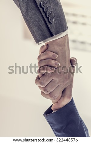 Retro image of business partners - man and woman shaking hands to close a deal, in agreement, greeting or congratulations, view from underneath their hands. - stock photo