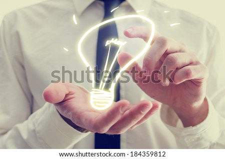 Retro image of businessman holding a creative light bulb icon in his hands conceptual of ideas, inspiration, imagination, and innovation. - stock photo