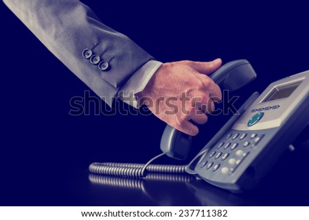 Retro image of businessman making a phone call holding the handset receiver of a telephone in his hand , close up view of his hand in a suit. - stock photo