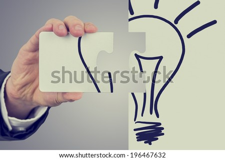 Retro image of businessman with the idea for business development holding two pieces of a jigsaw puzzle bearing the image of a light bulb ready to fit them together to find the perfect idea. - stock photo