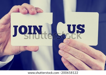 Retro image of male hand  holding words Join us  split over two puzzle pieces.  - stock photo
